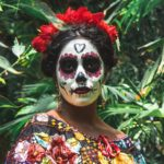 standing woman with painted face surrounded by green plants