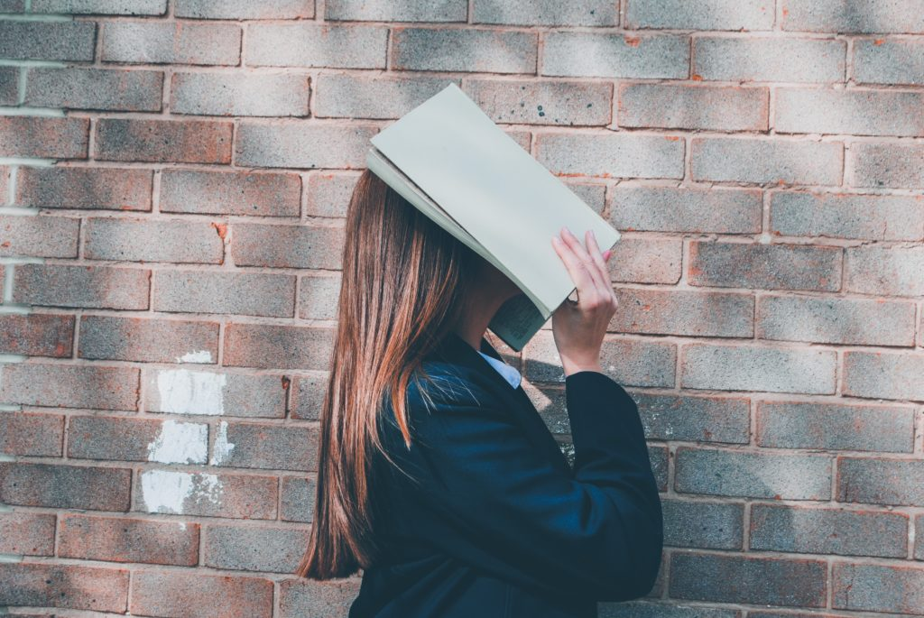 woman covering her face with a book