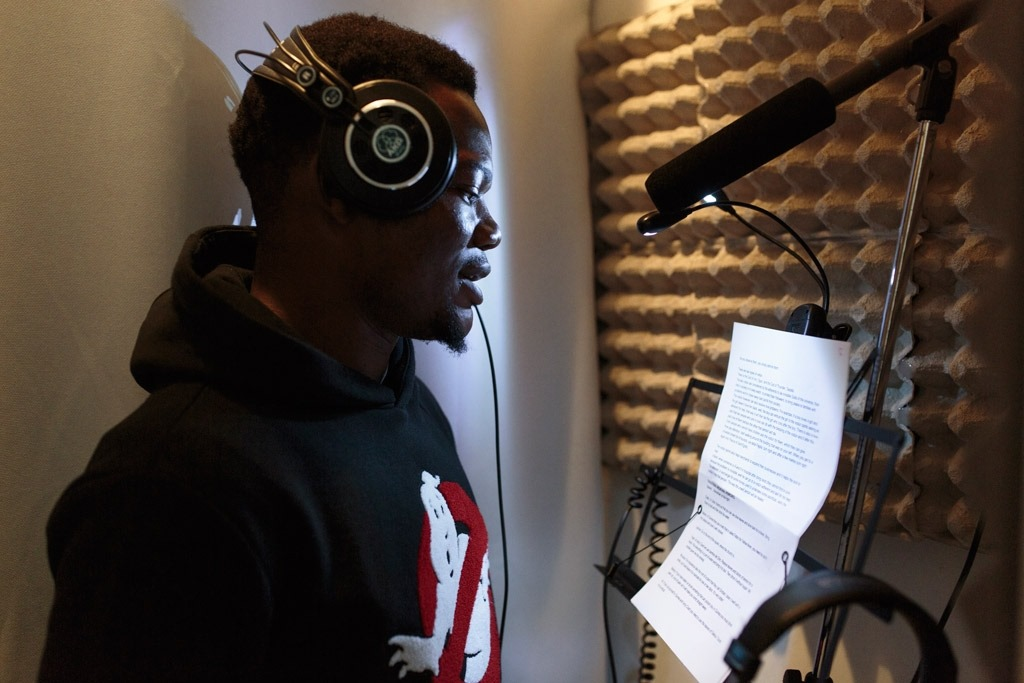 young person with headphones in front of a mic reading a script